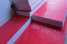 A stack of red covered books. They have a faint design on them. In the left hand upper corner of the book, it reads The Business of Graphic Design: The RGD Professional Handbook
