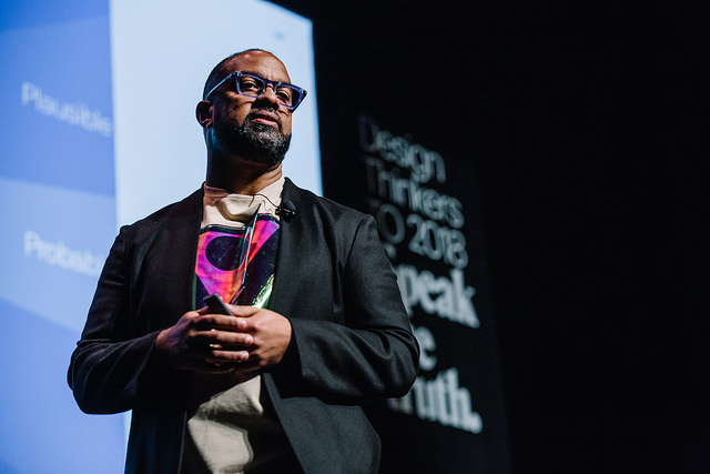 A Black man in a black blazer and a colourful shirt is on a stage. There is a screen behind him. He is wearing glasses and he has a short beard.