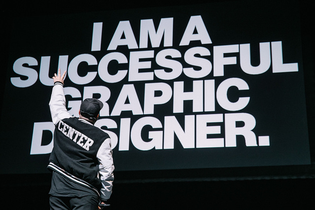 "A man with his back to a screen that says ""I am a successful graphic designer.\"""
