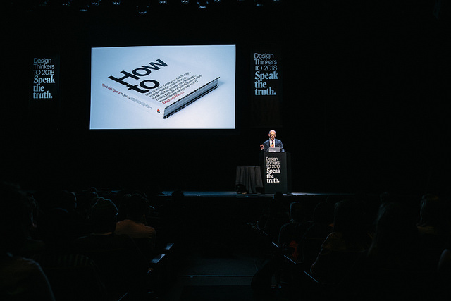 "A far-away shot of a man on a stage, speaking behind a podium. There is a screen on the stage and a book is shown on the screen. The book is titled ""How to\""."