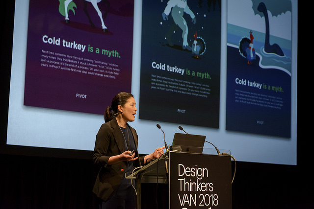 An image of a Korean woman standing in front of a podium, speaking. Behind her there is a screen with three images on it; all of the images have different designs and they say cold turkey is a myth.