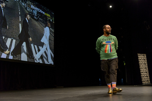 A Black man wearing a green sweater, dark pants, colourful socks, and gold shoes is on stage with his arms behind him. There is a screen behind him with an image of men walking a long a crosswalk.