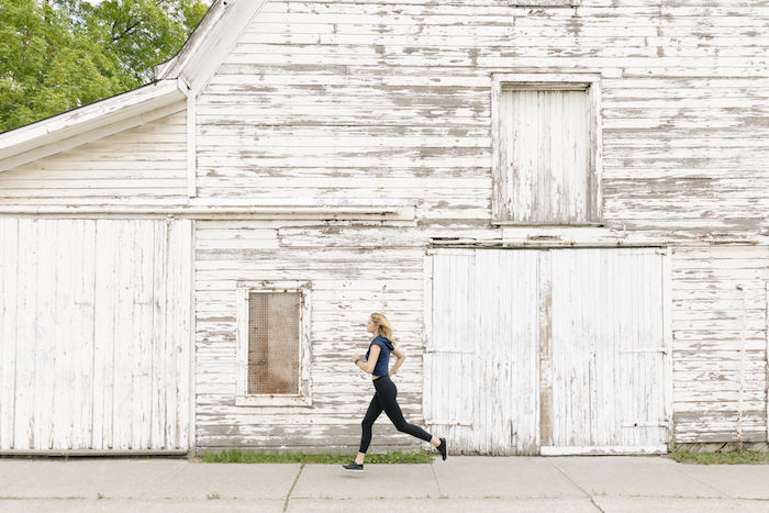 Woman running beside a whitewashed old barn