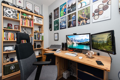 A photo of an office. In the office is a bookcase, a desk with two computer monitors, and lots of photos on the walls.