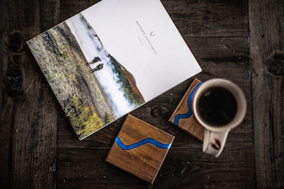 Coasters, a mug with coffee in it and a catalogue sit on a wooden table.