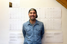 A man in a blue denim shirt and a backwards baseball cap is smiling at the camera. He is standing in front of a white wall with different white papers on it.