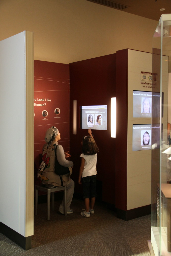 Woman and child using a touchscreen at the exhibit