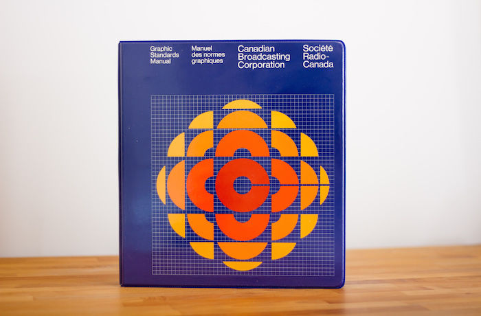 An image of a blue book with a red, yellow, and orange circular design on it. The book is sitting upright on a light wooden table.