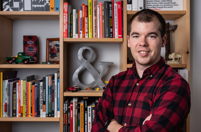 A man in a red and black checked shirt stands in front a bookshelf. His arms are crossed. He is smiling. He has dark brown, short hair and light skin.
