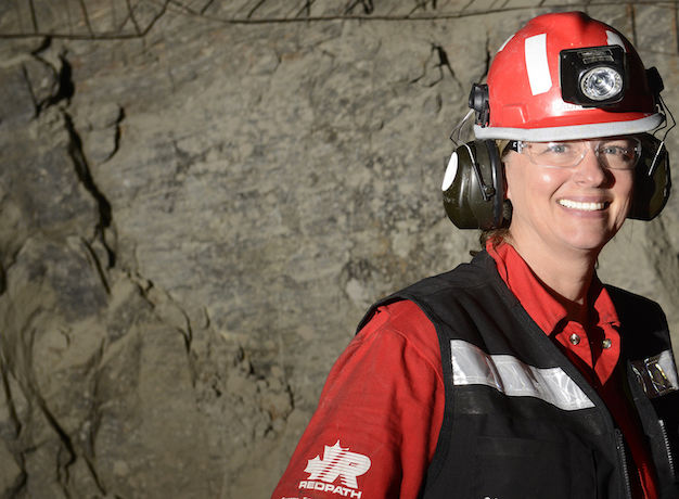 A woman wearing construction-like gear with a hard hat and safety glasses smiles at the camera