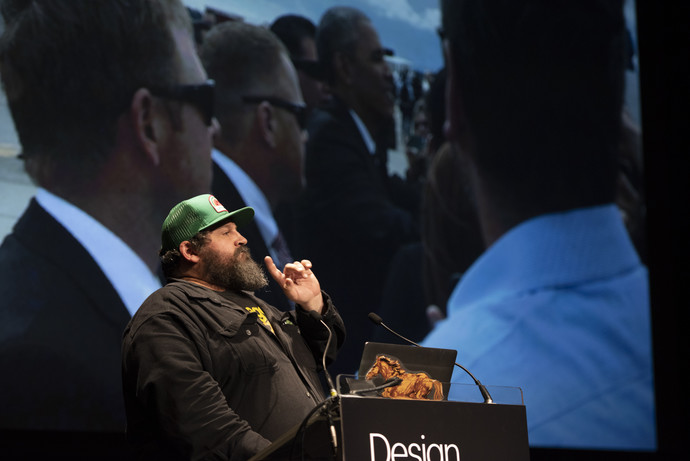 A man with a beard and a green hat is standing at a podium, talking. On the screen behind him is a photo of men in suits with sunglasses on.