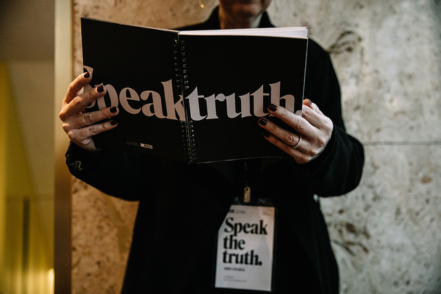 A person with red nail polish is holding a book that says \'Speak\' and \'Truth\' on the cover. The photo cuts off at the person\'s chin so their face isn\'t visible.