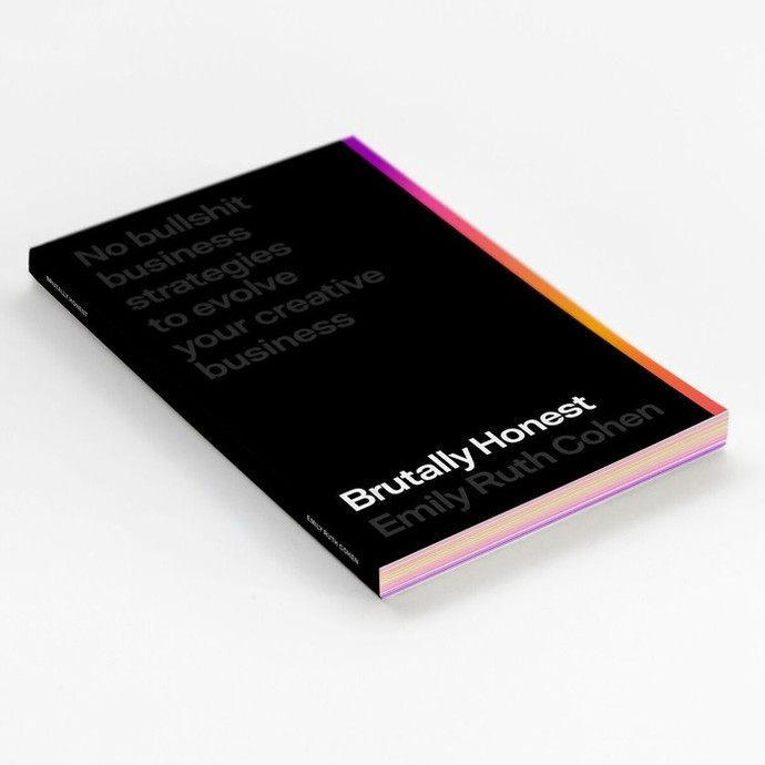A black book with colourful pages. White and grey text is on the cover.