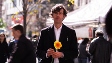 A man holding a yellow and orange flower while standing in a crowd of people.