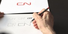 A hand is drawing the letters C and N. The letters are the logo for CN Rail.
